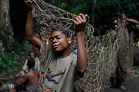 Sorting out the nets after the hunt...These folks all had shelter for the night in about two hours.  Women bend the branches to create a superstructures and then go off in the woods to get the right kind of leaves.  The Forest Hunting camps we hiked to are about 10k to the camp and then another 10K to where they string their nets.   Boys who are going thru the end of the circumcision ceremony called Kumbi accompanied the other Pygmies to the camp and were housed off to the side.  They were whipped every morning and then sent off into the forest to hunt or fish.