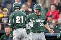 Michigan State Spartans first baseman Zack McGuire (55) greets teammate Dan Chmielewski (21) after scoring against the Michigan Wolverines during the NCAA baseball game on April 18, 2017 at Ray Fisher Stadium in Ann Arbor, Michigan. Michigan defeated Michigan State 12-4. (Andrew Woolley/Four Seam Images)