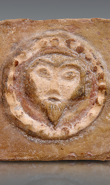 Detail of a 6th-7th Century Eastern Roman Byzantine  Christian Terracotta tiles depicting Christ - Produced in Byzacena -  present day Tunisia. <br /> <br /> These early Christian terracotta tiles were mass produced thanks to moulds. Their quadrangular, square or rectangular shape as well as the standardised sizes in use in the different regions were determined by their architectonic function and were designed to facilitate their assembly according to various combinations to decorate large flat surfaces of walls or ceilings. <br /> <br /> Byzacena stood out for its use of biblical and hagiographic themes and a richer variety of animals, birds and roses. Some deer and lions were obviously inspired from Zeugitana prototypes attesting to the pre-existence of this province's production with respect to that of Byzacena. The rules governing this art are similar to those that applied to late Roman and Christian art with, in the case of Byzacena, an obvious popular connotation. Its distinguishing features are flatness, a predilection for symmetrical compositions, frontal and lateral representations, the absence of tridimensional attitudes and the naivety of some details (large eyes, pointed chins). Mass production enabled this type of decoration to be widely used at little cost and it played a role as ideograms and for teaching catechism through pictures. Painting, now often faded, enhanced motifs in relief or enriched them with additional details to break their repetitive monotony.<br /> <br /> The Bardo National Museum Tunis, Tunisia.   Against a grey background.