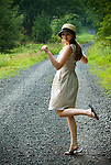 Young woman kicking up her heels on gravel country road