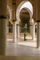 Senegal, Touba.  Woman Passing through Prayer Halls for Overflow Crowds at the Grand Mosque.