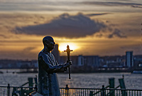 The sun is setting behind the World Harmony Peace Statue which has a face mask, Cardiff Bay, Wales, UKby St David's Hotel in Cardiff Bay, Wales, UK. Tuesday 15 December 2020