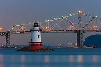 Twilight view of the Tarrytown Lighthouse and Tappan Zee Bridge on the Hudson River near the village of Sleepy Hollow, New York, with the skyline of Manhattan approximately 25 miles away in the background.