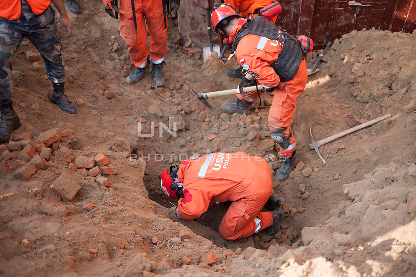 Rescue workers search for survivors under the rubble in a collapse site in Pathan, Kathmandu, Nepal.