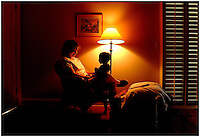 A woman interacts with a child during a quiet moment in a bedroom or livingroom.  Model released image may be used to illustrate other destinations or concepts.