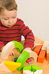 Two year old toddler boy pushing toy car through tunnel of blocks