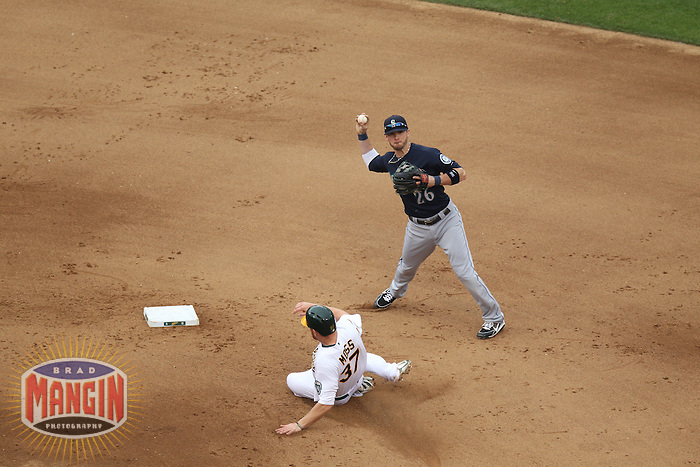 OAKLAND, CA - JUNE 15:  Brendan Ryan #26 of the Seattle Mariners turns a double play at second base forcing out Oakland Athletics base runner Brandon Moss #37 during the game at O.co Coliseum on Saturday June 15, 2013 in Oakland, California. Photo by Brad Mangin