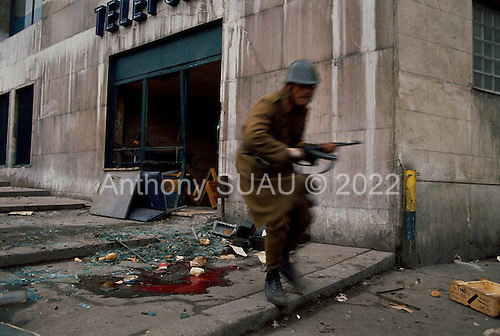 """Bucharest, Romania<br /> December 24, 1989<br /> <br /> An anti-Ceausescu militia exposes himself to pro-Ceausescu Securitate snipers fire.<br /> <br /> The week-long series of violence that overthrew the Communist regime of Nicolae Ceausescu, ended in a trial and execution of Ceausescu and his wife Elena by firing squad. Romania was the only Eastern Bloc country to violently overthrow its Communist regime or to execute its leaders.<br /> <br /> The Romanian populace was dissatisfied with the Communist regime and leader Ceausescu's economic and development policies were blamed for the country's shortages and widespread poverty. The powerful secret police (Securitate) controlled what was essentially a police state. Ceausescu was not pro-Soviet but """"independent"""" on foreign policy. He imitated the hard-line, megalomania, and personality cults of communist leaders like North Korea's Kim Il Sung."""