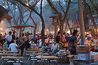 Outdoor restaurant tables and busy street market in Daqingzhen Si, Muslim District, Xian, Shaanxi, China.