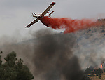 A single engine air tanker drops retardant on a 150-acre fire near Holbrook Junction, Nev., on Saturday, Sept. 10, 2011. Dozens of homes were initially threatened by the blaze but firefighters have caught the fire and an estimated 250 personnel are on scene..Photo by Cathleen Allison