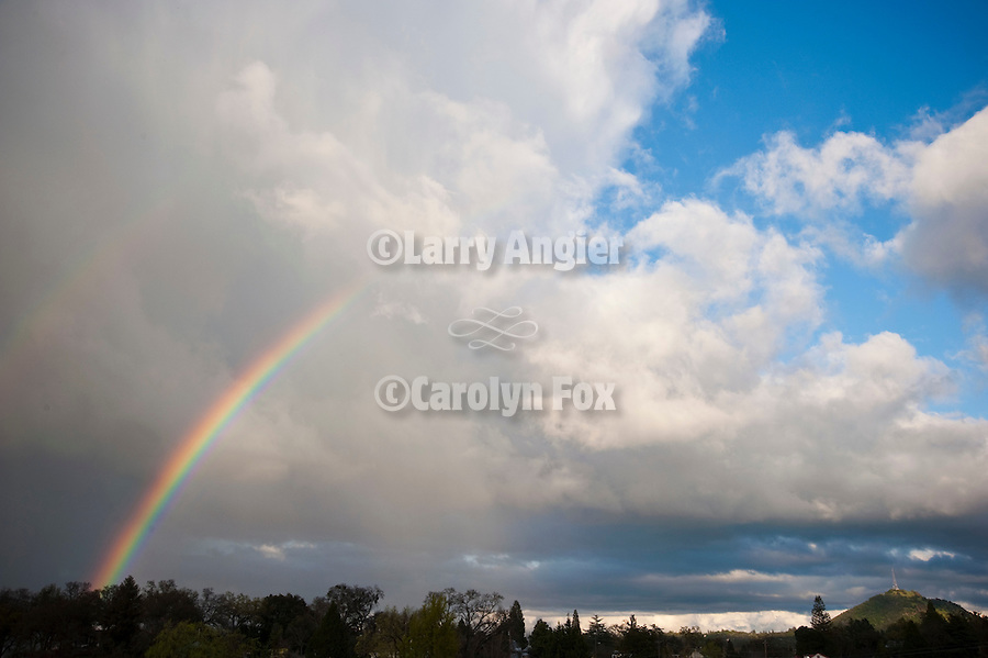 Spring rainbow and clouds at sundown over Jackson, Calif.