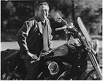 Barry Hannah poses on a his motorcycle outside his house in Oxford, Miss.