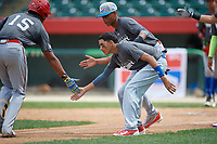 Bayron Lora (15) low fives Josue Payano (4) and Wilmin Candelario (5) as he rounds the bases after hitting a home run during the Dominican Prospect League Elite Underclass International Series, powered by Baseball Factory, on August 31, 2017 at Silver Cross Field in Joliet, Illinois.  (Mike Janes/Four Seam Images)