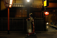 Geisha rush to an appointment in the Gion District of Kyoto.  Geisha are kimono clad women of esquisite grace and refinement who serve and entertain patrons in hidden tea houses and resteraunts charging over a 100 US$ a time, their lives and rituals are secretive and reserved for rich Japanese only.