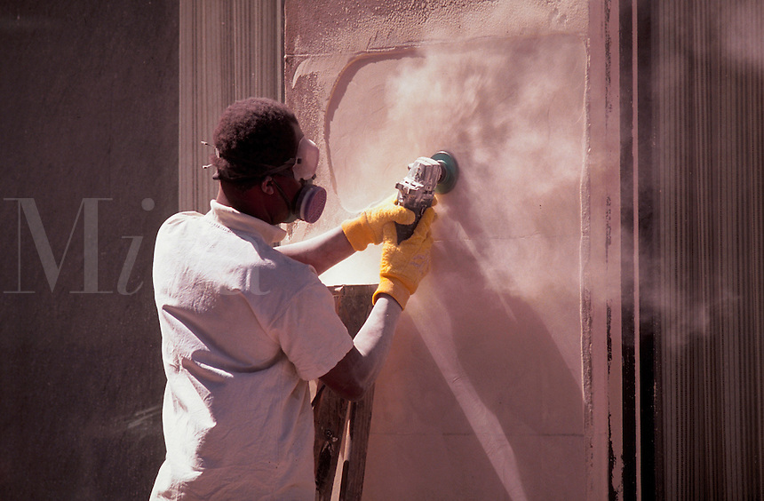 Man sanding a plaster wall, wearing a safety mask.