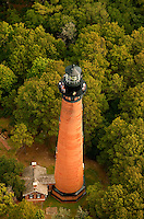 Aerial photography of Currituck Beach Lighthouse, located on the Outer Banks in Corolla, North Carolina. Currituck Light is one of the few lighthouses in the NC Outer Banks that allows visitors to climb to the top. With its red brick exterior, the lighthouse is  an example of Gothic Revival architecture. Located in the town of Corolla, the Currituck Beach Light was the last of four beacons placed at intervals from Cape Henry, Virginia to Cape Hatteras. Like other lighthouses on the North Carolina coast, the Corolla Lighthouse / Currituck Beach Lighthouse still aids ships in navigation. Charlotte NC photographer Patrick Schneider has extensive photo collections of the following lighthouses: Bodie Island Lighthouse, Bald Head Island Lighthouse, Cape Fear Lighthouse, Cape Hatteras Lighthouse, Cape Lookout Lighthouse, Currituck Beach Lighthouse, Diamond Shoal Lighthouse, Federal Point Lighthouse, Oak Island Lighthouse, and Ocracoke Lighthouse on Ocracoke Island.