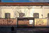 Milano, quartiere Bovisa, periferia nord. Una fermata ATM dell'autobus di fronte a un vecchio capannone industriale --- Milan, Bovisa district, north periphery. A bus stop in front of an old industrial shed