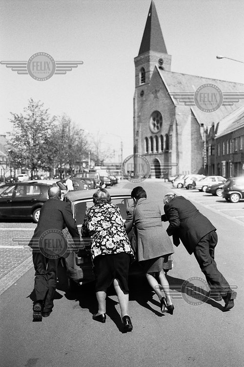 Two men and two women pushing a broken down DAF across a village parking lot.