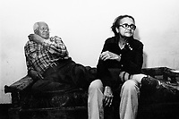 """USA. New York City. Spanish Harlem. Alejandro, a senior citizen and an immigrant from Puerto Rico and his wife Juanita, an immigrant from Santo Domingo, are both seated on a sofa. The family lives below the poverty line and receives public assistance (AFDC, Home Relief, Supplemental Security Income and Medicaid). The family resides in units managed by the New York City Housing Authority (NYCHA) which provides housing for low income residents. NYCHA administers rental apartments in facilities, popularly known as """"projects"""". Spanish Harlem, also known as El Barrio and East Harlem, is a low income neighborhood in Harlem area. Spanish Harlem is one of the largest predominantly Latino communities in New York City. 20.04.86 © 1986 Didier Ruef"""