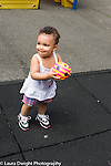 14 month old toddler girl outside at playground holding ball