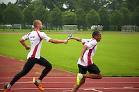 Switzerland. Canton Ticino. Tenero. Centro Sportivo Nazionale della Gioventù - Tenero (CST). Nationales Jugendsportzentrum Tenero. Alain Enz (L) and Yanier Bello (R) are training  under the rain. The 4 × 100 metres relay or sprint relay is an athletics track event run in lanes over one lap of the track with four runners completing 100 meters each. A relay baton is carried by each runner and must be passed within a 20 m changeover box (usually marked by yellow lines) which extends 10 m on either side of each 100 m mark of the race. 31.05.11 © 2011 Didier Ruef