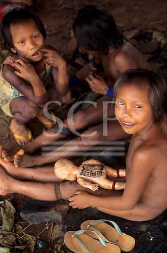 A-Ukre, Brazil. Kayapo Indian girls playing with carved wooden doll with black genipapo body paint. Para State.