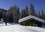 Deutschland, Bayern, Chiemgau: Schneelandschaft auf der Winklmoosalm - Mann vor einer Almhuette | Germany, Bavaria, Chiemgau: winter landscape at Winklmoosalm - alpine pasture hut and man hiking
