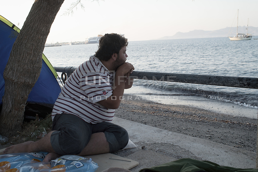 Syrian near his tent where he sleeps in the streets among tourists is looking at the sea on the island of Kos, Greece Sept 2015