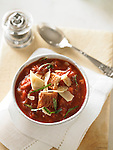 Bowls of a thick tomato soup with cubes of bread and shaved parmesan cheese.