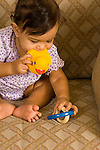 7 month old baby girl sitting biting duck toy and reaching with other hand to pick up toy