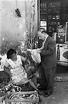 Mexico 1970s  man food shopping checking if the chicken is plump. 1973 Oaxaca de Juárez