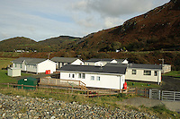 Low lying properties in the village of, on the Cardigan Bay coast, Gwynedd, north Wales, UK which is threatened by the policy of 'managed retreat' of the coastal sea defences.