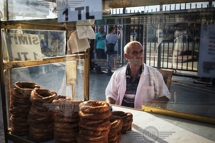 A man sits next to his mobile simit stall (circular bread encrusted with sesame seeds).