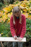 Mädchen baut einen Vogel-Nistkasten aus Brettern, 1. Schritt: Aufzeichnen