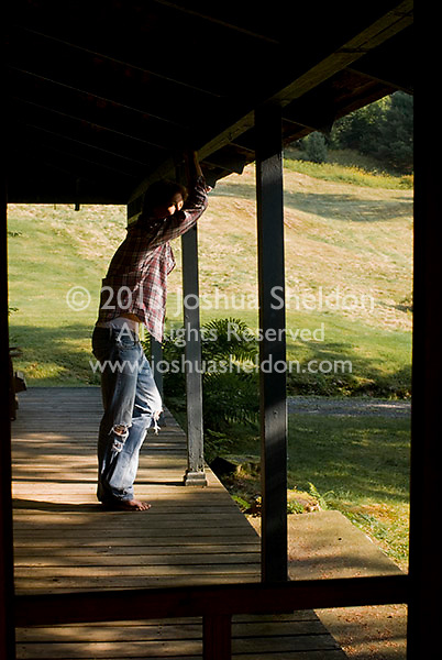 Young man seen through screen door, standing on porch