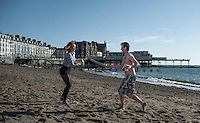 Aberystwyth, West Wales, UK Weather: Two young people sword-fighting on the beach in in Aberystwyth, Wales, UK