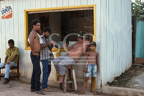Acre State, Brazil. Men and boys at the window of a rural provisions shop in a wooden shack.