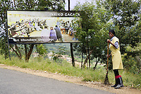 """Rwanda. Southern province. Gitarama. District of Muhanga. A black woman sweeps up dirt on the side of the concrete road. Giant advertisement board for the Gacaca jurisdiction. The Gacaca (pronounced """"gachacha"""") court is part of a system of community justice inspired by tradition and established in 2001 in Rwanda, Rwanda implemented the Gacaca court system, which has evolved from traditional cultural communal law to enforcement procedures and prison condemnation. © 2007 Didier Ruef"""