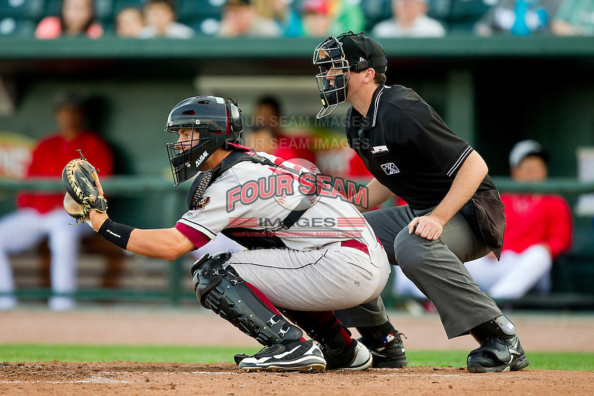 Wisconsin Timber Rattlers catcher Clint Coulter (12) sets a target as home plate umpire Nate Tomlinson looks on during the Midwest League game against the Great Lakes Loons at the Dow Diamond on May 4, 2013 in Midland, Michigan.  The Timber Rattlers defeated the Loons 6-4.  (Brian Westerholt/Four Seam Images)