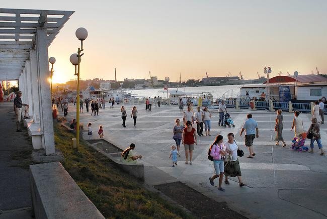 ROMANIA, Tulcea, 2010/08/24.Tulcea is the real gateway to the Danube Delta. It is also an industrial city of 100,000 inhabitants. Can be seen in the background shipyards. This Sunday evening at the end of the summer, walk along the river is frequented by families and lovers..© Bruno Cogez..Roumanie, Tulcea, bord du Danube, 24/08/2010.Tulcea, véritable porte du delta du Danube, est aussi  une ville industrielle de 100000 habitants. On aperçoit en arrière plan les chantiers navals. Ce dimanche soir de la fin de la période estivale, la promenade le long du Danube est fréquentée par les familles et les amoureux..© Bruno Cogez