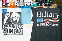"""A vendor sold Bernie Sanders-themed t-shirts alongside a """"Hillary For Prison"""" t-shirt outside the secure area surrounding the Democratic National Convention at the Wells Fargo Center in Philadelphia, Pennsylvania, on Wed., July 27, 2016. """"Hillary For Prison"""" has been a common slogan at Republican campaign events during the election cycle."""