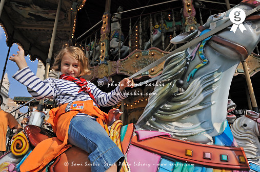 Girl waving and smiling on merry-go-round (Licence this image exclusively with Getty: http://www.gettyimages.com/detail/85071261 )