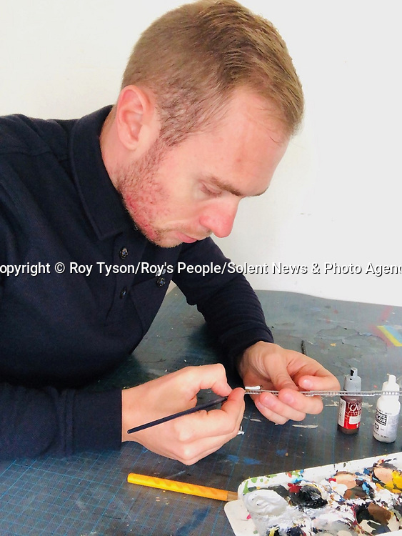 Pictured:  Roy painting one of his figures<br /> <br /> Tiny figurines give a new perspective on everyday objects as they are posed interacting with them in their miniature world.  Artist Roy Tyson creates witty and intriguing imagery with customised miniature figures, under the name Roy's People.<br /> <br /> Since 2012, he has been photographing his miniature world on the streets of London and beyond.  SEE OUR COPY FOR DETAILS.<br /> <br /> Please byline: Roy Tyson/Roy's People/Solent News<br /> <br /> © Roy Tyson/Roy's People/Solent News & Photo Agency<br /> UK +44 (0) 2380 458800