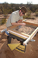 Jeff Charest from Rhode Island.a university of arizona senior.scans his screening of dirt from.the Marana Platform mound looking for.shards and other artifacts from the .mound occupied for 100 years by the HoHoKam.people from 1200 ad to 1300 ad...