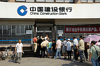 People line up to enter a China Construction Bank branch in the early morning Beijing, China..