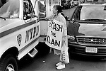 MANHATTAN , NEW YORK USA JUNE 1999: WOMAN AT AN ANTI KLU KLUX KLAN RALLY HANDS A FLOWER TO NYPD NEW YORK POLICEMAN WHO IS SITTING IN HIS POLICE VAN. SHE IS WEARING A SMASH THE KLAN BANNER AROUND HER NECK. NEW YORK NEW YORK JUNE 1999.