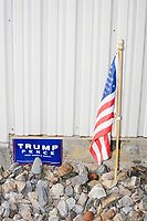 A Trump/Pence campaign sign and an American flag are seen among rocks outside a Make America Great Again Victory Rally with US President Donald Trump in the final week before the Nov. 3 election at Pro Star Aviation in Londonderry, New Hampshire, on Sun., Oct. 25, 2020.