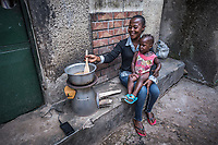 Uganda, Hoima. Hope Lydia Businge, 26 years, has a two year old daughter and runs a hair salon. At home she uses a BioLite cook stove that charges a light and mobile phone. Cooking on the Biolite stove at home with her daughter.