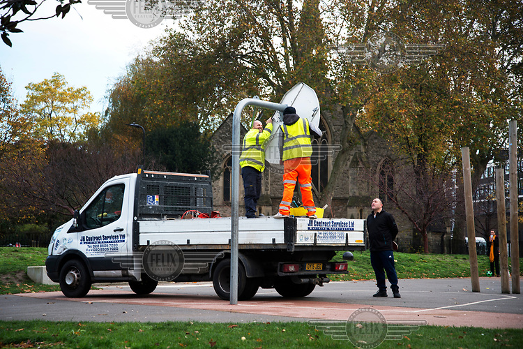Contractors remove a basketball hoop from a park in Hackney so people cannot gather to play during the November lockdown.
