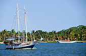 Porto Seguro, Brazil. Two-masted pleasure boat on the way to Monte Pascoal past palm fringed beaches. Bahia State.